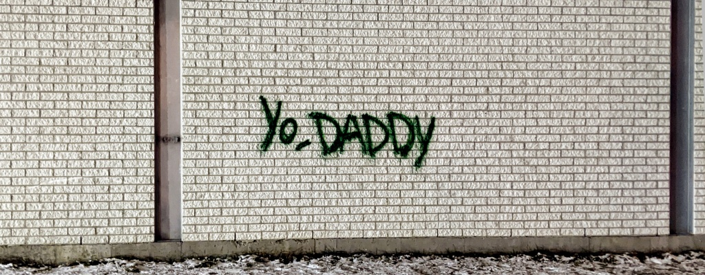 "Graffiti on a brick wall that reads ""Yo, daddy"""